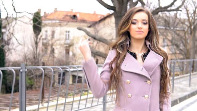 vídeos y material grabado en eventos de stock de hermosa chica mira a pie de la ciudad - moda de otoño