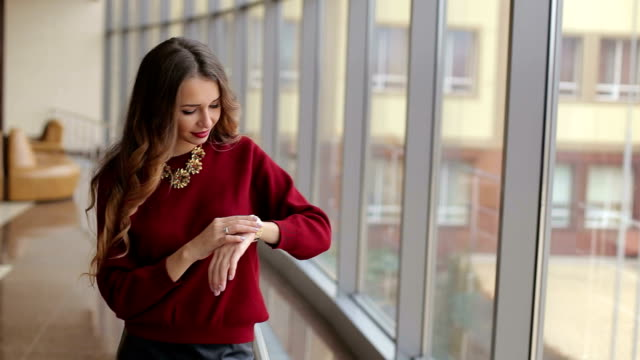 Beautiful girl looks at her watch. Young attractive girl looking time in the airport near the window. The girl admires the watch. Beautiful girl looks at her watch. Young attractive girl looking time in the airport near the window. The girl admires the watch. wristwatch stock videos & royalty-free footage