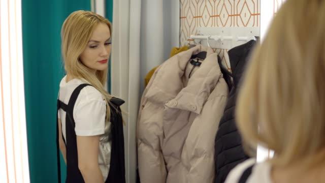 Beautiful girl looks dress on mirror in fitting room.