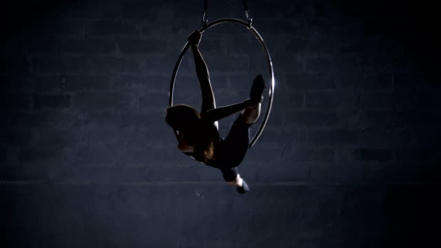 Beautiful girl makes a twine on the aerial hoop video
