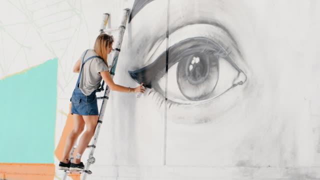 美しい少女は、都市の通りの壁にスプレーで大きな女性の顔の落書きを作るします。彼女は梯子の上に立っています。創造的な芸術。絵を描くデニム オーバー オールで才能のある学生 - street graffiti点の映像素材/bロール