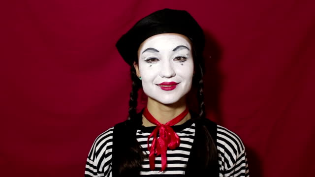 beautiful girl mime smiles and winks eyes while looking at the camera. beautiful girl in the image of mime winks and makes flirty movements with eyebrows looking at the camera. - гримировальные краски стоковые видео и кадры b-roll