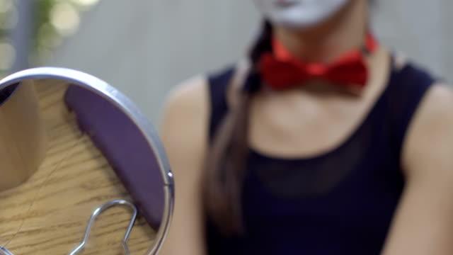 beautiful girl mime smiling sitting in the dressing room - гримировальные краски стоковые видео и кадры b-roll