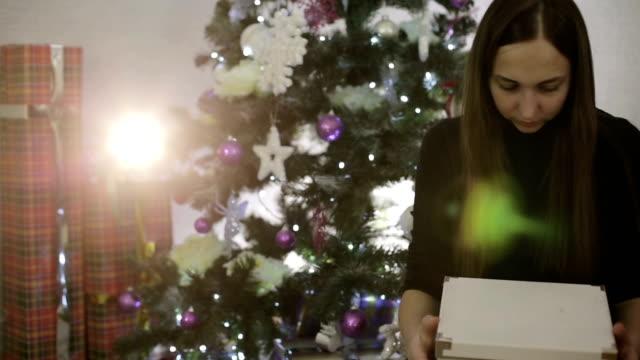 Belle jeune fille ouvre un cadeau de Noël dans la stupéfaction. - Vidéo