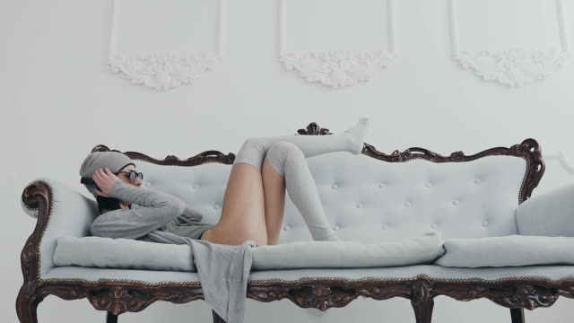 A beautiful girl or a woman dressed in gray long blouse and long gray stockings she lying on the couch to relax and listen music in the headphones, at the background in white wall, indoors