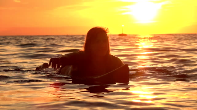 slow motion: beautiful girl paddling in the ocean on surfboard at golden sunset - pesche bambino video stock e b–roll