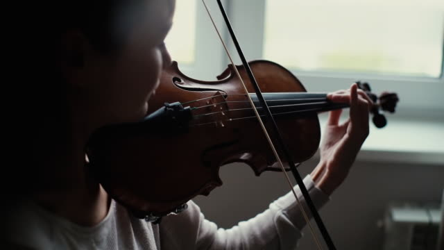 Beautiful girl plays the violin by the window in slow motion