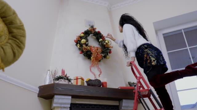stockvideo's en b-roll-footage met mooi meisje zich voorbereidt op kerstmis en siert de muur boven de open haard - christmas tree