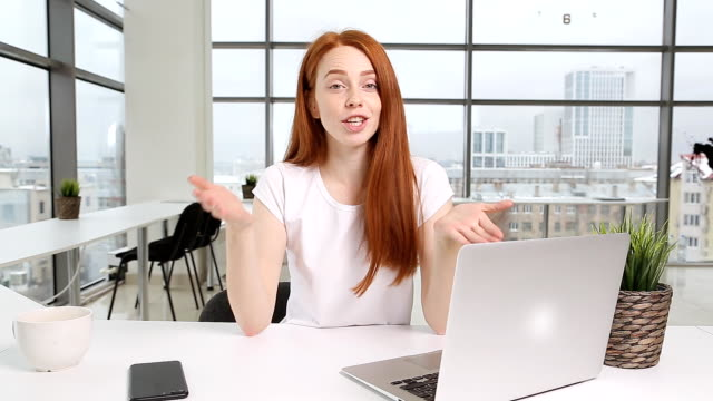 Beautiful girl recording video on camera at office. Fashion blogger concept video