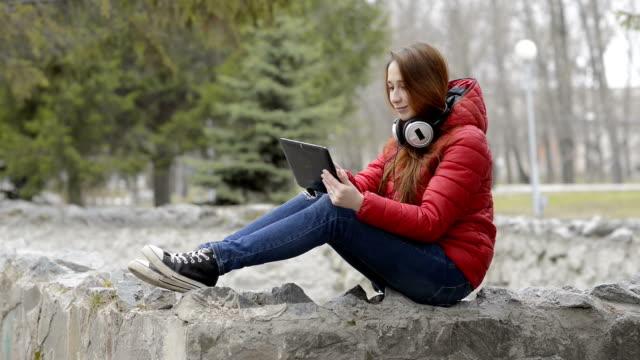 güzel kız istirahat ve eğlenceli tablet oynarken, şehir bahar park kafasına kulaklıklar ile oturuyor. kırmızı saçları ve kırmızı ceketi var. portre. yan görünüm. 29,97 fps. - dijital yerli stok videoları ve detay görüntü çekimi