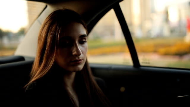 Beautiful girl riding in a taxi, reads the message on the tablet video