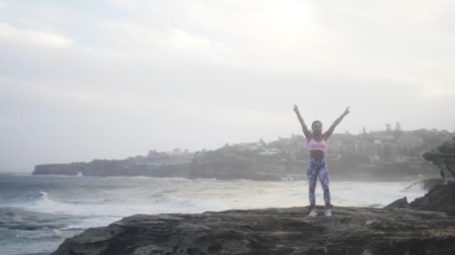 美しい女の子 (スローモーション) 海の近くの崖の上の彼女の腕を上昇します。 - 女性選手点の映像素材/bロール
