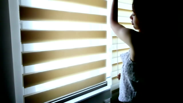Beautiful girl rolling up the blind in the morning video