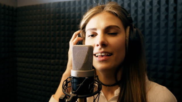 Beautiful girl sings in sound studio and enjoying process. Young singer emotionally recording new song. Lady sings to microphone. Working of creative musician. Show business concept. Slow motion Close up