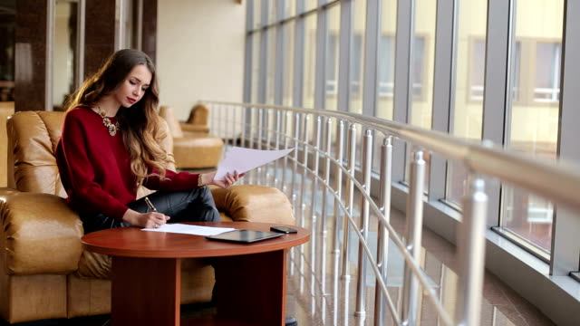 Beautiful girl sitting at table with documents in a modern building. Beautiful girl sitting at table with documents in a modern building. Business girl with papers in a cafe bay window stock videos & royalty-free footage