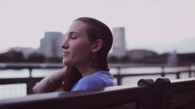 A beautiful girl sitting on a bench in front of a cityscape, slow motion