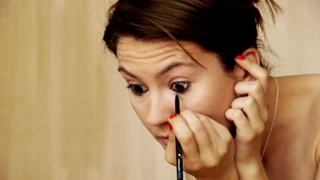 Beautiful Girl smiling brightly making up. Using eyeliner left eye Beautiful Girl smiling brightly when making up. Using eyeliner with her left eye lip liner stock videos & royalty-free footage