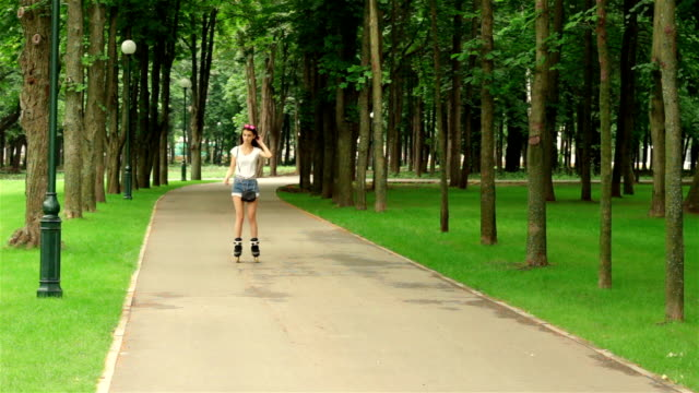 beautiful girl smiling goes rollerblading and straightens hair beautiful young girl smiling goes rollerblading and straightens hair charming stock videos & royalty-free footage