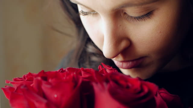 Beautiful girl sniffs a bouquet of red roses and then looks out the window. Closeup Beautiful girl sniffs a bouquet of red roses and then looks out the window. Closeup smelling stock videos & royalty-free footage