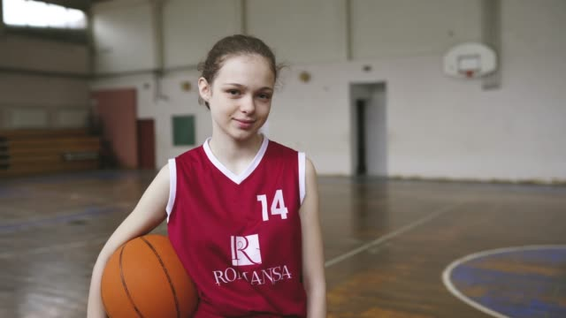 Beautiful girl standing in front of coach and teammates on practice