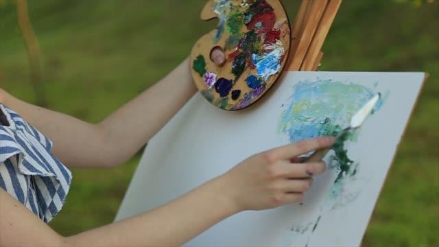 beautiful girl standing in the park and draws a picture using a palette with paints and a spatula. - szpatułka przybór do gotowania filmów i materiałów b-roll