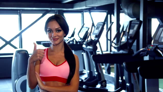 Beautiful girl stands in the gym and shows thumbs up - video