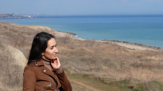 A beautiful girl stands on a cliff on a background of blue ocean. A bright sunny day and the sea.