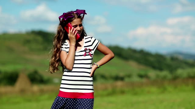 Beautiful girl stands on the meadow and speaks on cell phone video