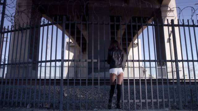 Beautiful girl staying and positing near the fence under the bridge. Industrial area fashion videoshoot video