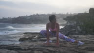 istock Beautiful girl stretches on the cliff near the ocean (slow motion) 913375678