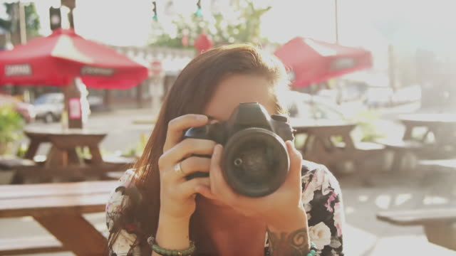 A beautiful girl taking pictures with a camera, slow motion