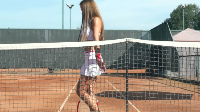 Beautiful girl tennis player. Beautiful girl on the tennis court with a racket for playing tennis. She smiles and gently rubs her hand over the stretch mesh. russian ethnicity stock videos & royalty-free footage