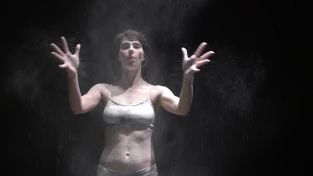 暗闇の中でほこりビデオを投げる美しい女の子 ビデオ