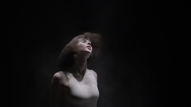 暗闇の中でダストビューを投げる美しい女の子 ビデオ