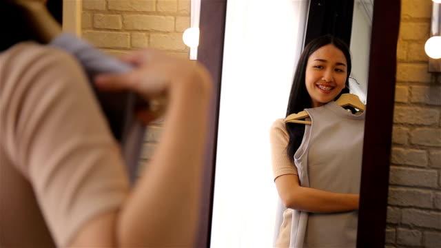 schönes mädchen versucht kleid in der nähe von spiegel im zimmer - kleid stock-videos und b-roll-filmmaterial