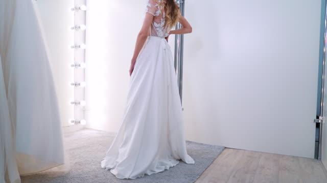 vacker tjej försöker på lyxklänning i bröllopssalong - aftonklänning bildbanksvideor och videomaterial från bakom kulisserna