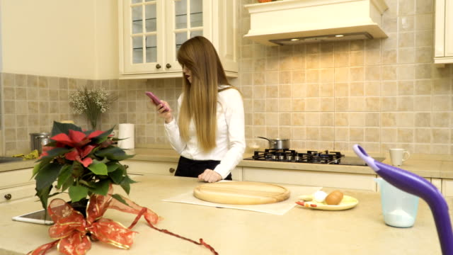 Beautiful girl uses phone at the kitchen video