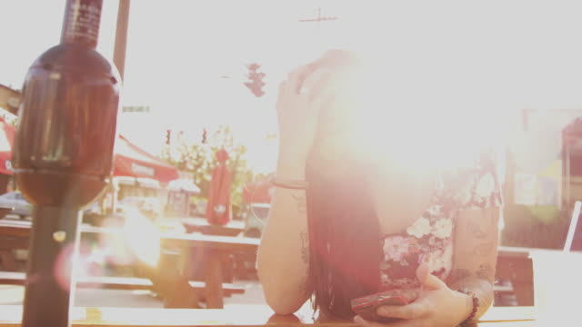 A beautiful girl waiting at an outdoor table and using her phone, slow motion