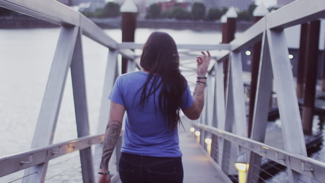 A beautiful girl walking away from the camera toward a boat dock and looking back, slow motion