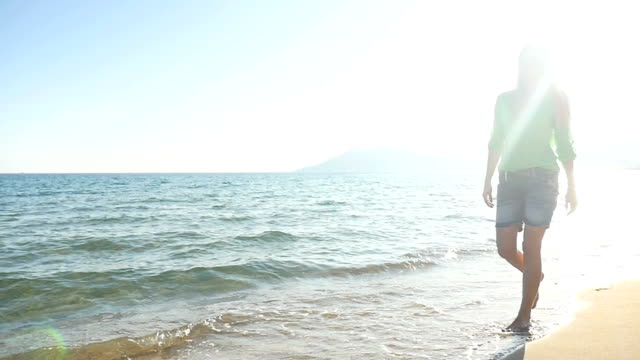 Beautiful girl walking barefoot along the sea video