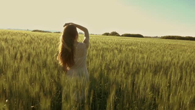 Beautiful girl walking in wheat field, slow motion