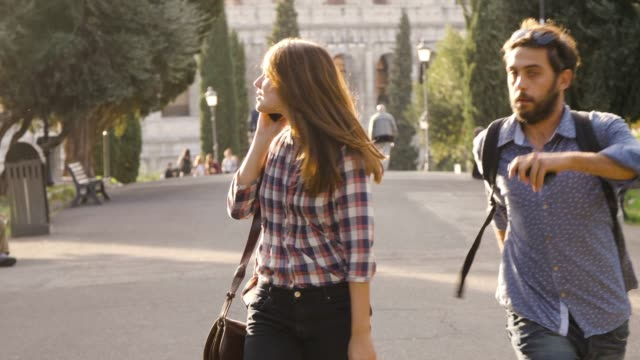 beautiful girl walks in park road on a phonecall and attractive young man boyfriend behind her taps shoulder run funny prank trees colosseum in background in rome at sunset - viaggiare zaino in spalla video stock e b–roll