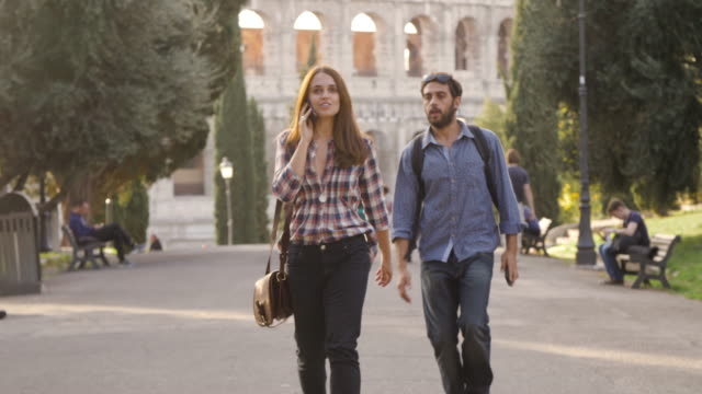 beautiful girl walks in park road talking on phone and attractive young man boyfriend behind her taps shoulder run funny prank trees colosseum in background in rome at sunset lovely beautiful woman with long hair slow motion - viaggiare zaino in spalla video stock e b–roll