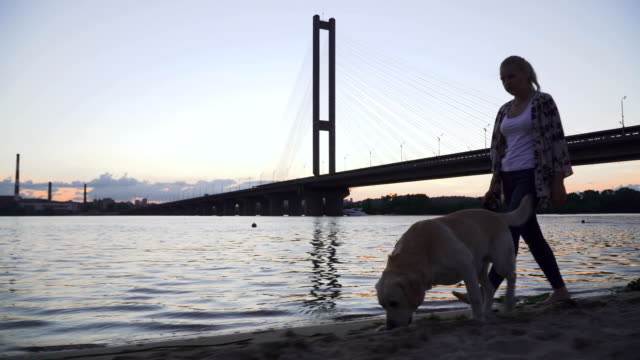 Beautiful girl walks with a dog along the river