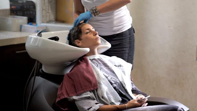 Schönes Mädchen wäscht den Kopf in einem Schönheitssalon – Video