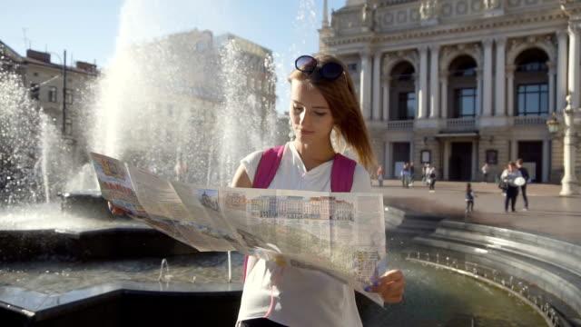 stockvideo's en b-roll-footage met mooi meisje kijken kaart in de buurt van fontein - wit t shirt