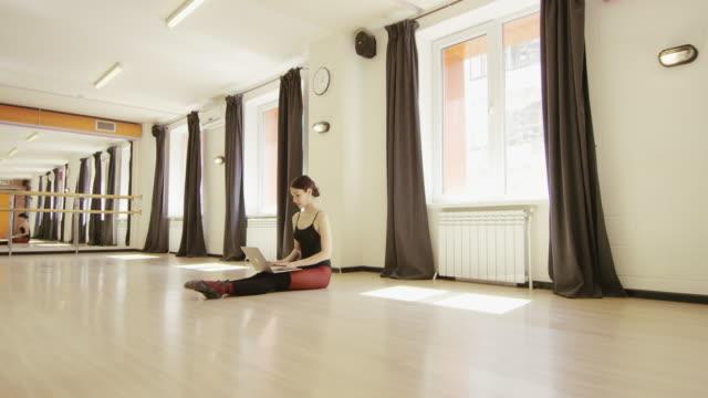 vacker flicka klädd balett bodyen med laptop - gympingdräkt bildbanksvideor och videomaterial från bakom kulisserna