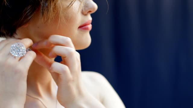 beautiful girl wears earrings - photosession video