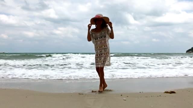 büyük şapka ile güzel kız sahilde bükülmüş - i̇nsan sırtı stok videoları ve detay görüntü çekimi