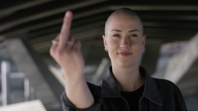 beautiful girl with buzz cut showing fuck you sign - бунтарство стоковые видео и кадры b-roll
